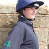 Sophie in a dark blue bespoke polo shirt with emerald green star design and matching lycra cap.